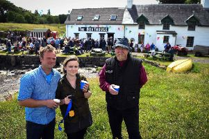 Ulva residents Rhuri Munro and his wife Rebecca and Barry George celebrate the buyout last week. Picture: Andy Buchanan/Getty Images