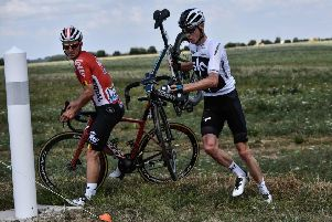 Chris Froome, right, carries his bike after falling into a ditch in the last kilometres of the first stage of the Tour de France. Picture: AFP/Getty Images