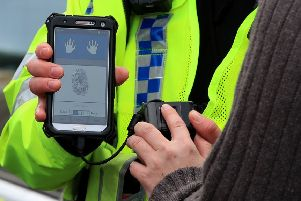 A police officer holding a new mobile fingerprint scanning system which allows police to identify a potential suspect in under a minute. Picture: PA