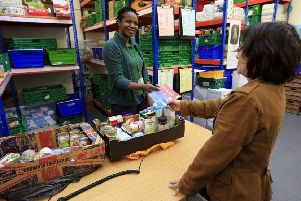 A foodbank manager gives a fuel voucher to a client at the Trussell Trust Brent Foodbank, Neasden, London. Picture: PA