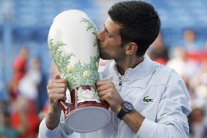 Novak Djokovic plants a big kiss on the Rookwood pottery trophy after his victory over Roger Federer in Cincinnati on Sunday. Picture: AP.