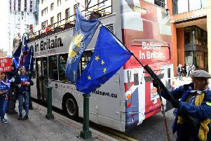 Anti-Brexit protestors carry EU flags as they stand alongside the Leave Means Leave battle bus parked outside a Tory conference fringe event. Picture: Getty
