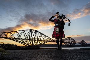 Piper Louise Marshall at dawn alongside the Forth Bridge at North Queensferry on the 100th anniversary of the signing of the Armistice which marked the end of the First World War. Picture: PA Wire