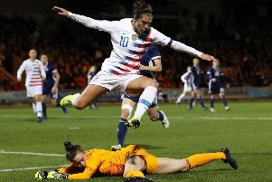USA striker Carli Lloyd leaps to avoid Lee Alexander as the Scots gave the World Cup holders a stiff test in Paisley last night. Picture: Getty Images