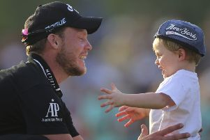 Danny Willett celebrates with his young son after his victory in the  World Tour Championship in Dubai. Picture: AP Photo/Kamran Jebreili