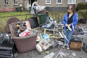 Mother-of-nine Donna Newby with the remains of her property which was dumped in garden in front of her flat when she came home to find she had been evicted. Picture: SWNS