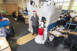 Jack Makepeace, 24 who has constructed a Christmas castle around his desk. Picture: SWNS