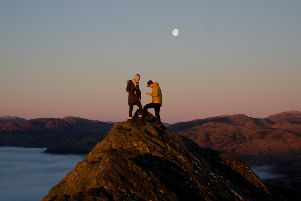 Photographer Rob Jamieson was on hand to capture the romantic moment when a man got down on one knee to propose to his partner on top of the mountain Ben A'an in the Trossachs. Picture: SWNS