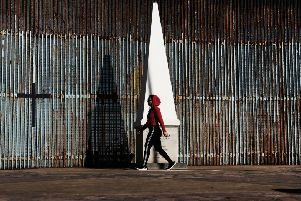 A woman walks past the border fence in the city of Tijuana, Mexico, on January 19, 2019 PIC: Spencer Platt/Getty Images