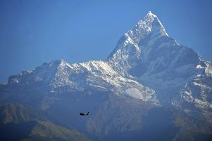 A plane flies by the mighty Mount Machhapuchhare (6,997m) in the Annapurna range near Sarangkot, Pokhara (Picture: Jane Barlow)