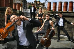 Members of the Catalonian string orchestra Orquestra de Cambra d'Emporda, who combine classical music with pop songs and mime, pose in Edinburgh (Picture: Jeff J Mitchell/Getty Images)