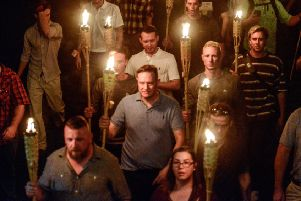 White nationalists, including Cole White, in the striped top to the right, participate in the torch-lit march on the grounds of the University of Virginia in Charlottesville. Picture: 'Stephanie Keith/Reuters