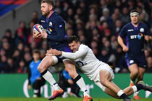 Finn Russell is tackled by England wing Jonny May. Picture: AFP/Getty Images