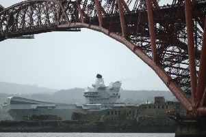 The 65,000 tonne HMS Queen Elizabeth Aircraft carrier goes under the Forth Rail Bridge