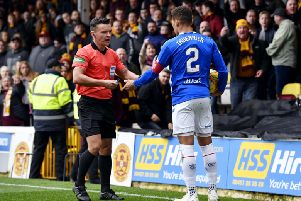 Rangers defender James Tavernier hands a lighter to referee Nick Walsh after it was thrown from the crowd. Picture: SNS