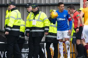 James Tavernier talks to referee Nick Walsh after objects thrown at him. Picture: SNS