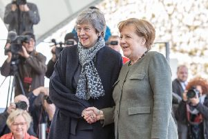 Theresa May and Angela Merkel shake hands for the cameras but the German Chancellor was not there to greet the UK leader when she first arrived (Picture: Omer Messinger/Getty Images)