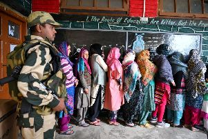 Kashmiri Muslim voters stand in a queue an as Indian Border Security (BSF) soldier walks past at a polling station during the first phase of India's general election in Handwara (Photo by Tauseef MUSTAFA / AFP)