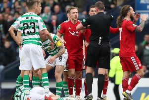 Referee Craig Thomson shows a red card to Dominic Ball as Ryan Christie lies injured on the turf. Picture: Getty