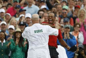 Tiger Woods celebrates  with his caddie, Joe LaCava, at Augusta on Sunday.