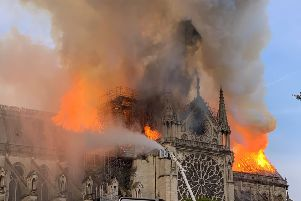 Flames and smoke are seen billowing from the roof at Notre-Dame Cathedral in Paris on April 15, 2019. (Photo by Patrick ANIDJAR / AFP)