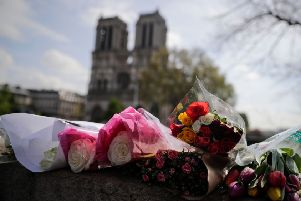 Flowers laid on a bridge in front of Notre-Dame following this week's devastating fire. Picture: AFP/Getty Images