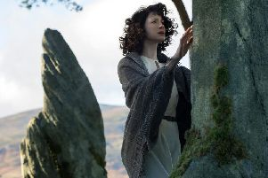Claire Randall Fraser, played by Caitriona Balfe, travels through hundreds of years in time after touching fictional standing stones at Craigh na Dun in the first season of Outlander.