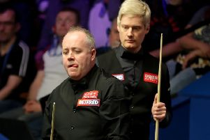 Neil Robertson keeps an eye on John Higgins, front, as the Scot contemplates a shot. Picture: Richard Sellers/PA Wire