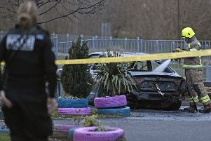 A black Audi A5 was found on fire a short time after the attack at Harperrig Way. Picture: Neil Hanna