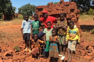 Everson Mapayani, Malawi's youngest councillor at 28, with some young helpers, as he collects bricks to build a youth and children's centre (Picture: Susan Dalgety)