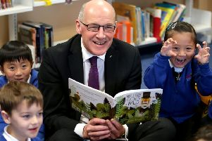 Education Secretary John Swinney reads to pupils in Edinburgh. Picture: Jane Barlow/PA