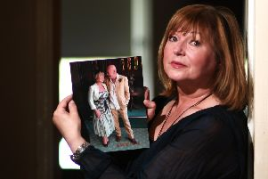 Portrait of Joan McLellan, who lost her husband, Ross, earlier this year. Joan is holding a wedding photograph of her and Ross.'' Pic: John Devlin