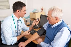 British doctor taking senior man's blood pressure in surgery room having a check up