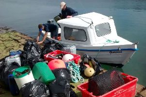 A boat owned by Kevin Byrne unloads bags of plastic rubbish like old fishing twine. Picture: SWNS