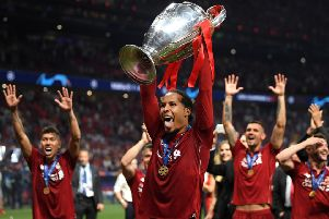 Virgil Van Dijk sticks his tongue out as he lifts the Champions League trophy. Picture: Getty.