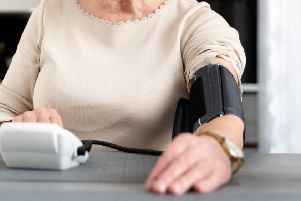 Woman measuring blood pressure at home