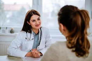 A young GP listening to a patient