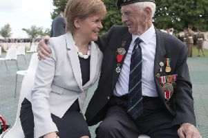 First Minister Nicola Sturgeon sits with D-Day veteran John Greig, 95, from Dumfries, at the Commonwealth War Graves Commission Cemtery in Bayeaux, France, ahead of commemorations for the 75th anniversary of the D-Day landings.