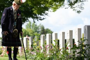 Veteran John Lamont looks at some of the gravestones ahead of the memorial service in Bayeux Cemetery on June 6.