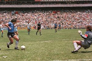 Maradona runs past English defender Terry Butcher on his way to dribbling goalkeeper Peter Shilton and scoring his second against England during the World Cup in 1986.