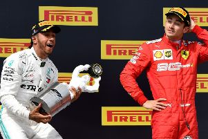 Lewis Hamilton celebrates on the podium with the French Grand Prix trophy as third-placed Charles Leclerc of Ferrari looks on. Picture: Gerard Julien/AFP