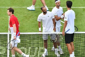 Andy Murray, left, and Marcelo Melo leave the court after losing their first-round match at Eastbourne.