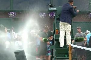 The sprinkler goes off knocking over a bin and sending the players fleeing.