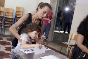 A woman holding her child casts her vote at a polling station during general elections on July 7, 2019 in Athens, Greece. The New Democracy party of Kyriakos Mitsotakis defeated Prime Minister Alexis Tsipras's Syriza party. (Photo by Milos Bicanski/Getty Images)