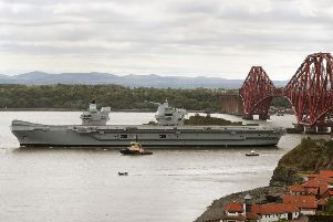 The aircraft carrier HMS Queen Elizabeth passes the Forth Bridge in 2019 following maintenance at Rosyth Dockyard. The ship was originally assembled at the Fife yard