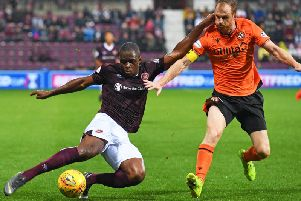 Hearts forward Uche Ikpeazu plays the ball under pressure from Mark Reynolds