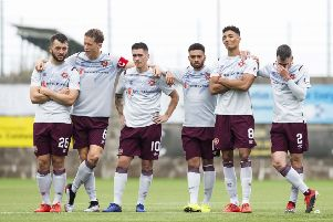 Hearts players stand dejected at the halfway line as the penalty shootout slips away from them. Picture: SNS.