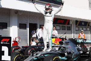 Lewis Hamilton leaps on to the bonnet of his car in celebration following his victory in Hungary. Picture: AP.