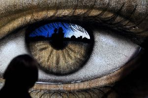 A girl walks past an eye drawn by British street artist My Dog Sighs. Picture: Getty Images