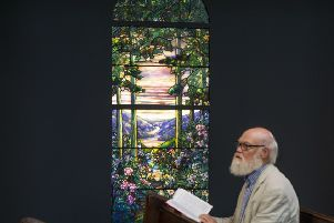 Christopher Gorman, a visitor to the abbey, reads nearby a window commissioned more than 100 years ago by the Scottish-American industrialist Andrew Carnegie